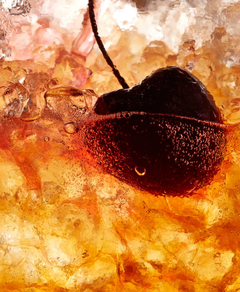 Cocktail photography with a cherry floating on crushed ice