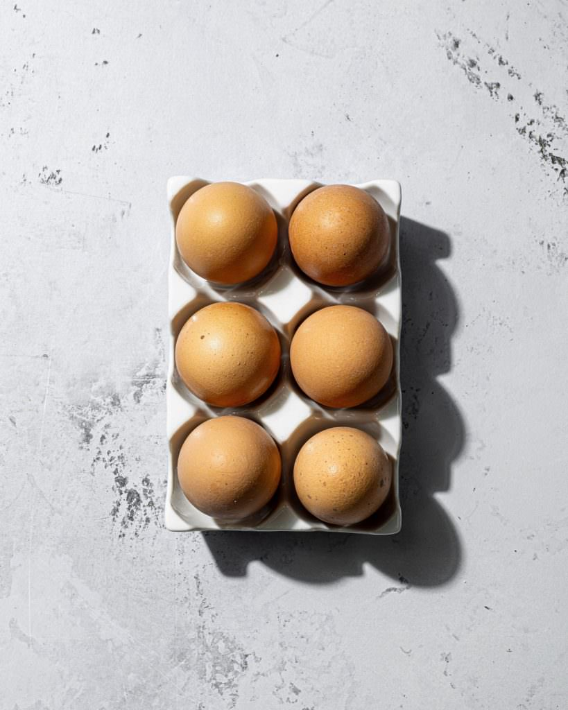 Chickens eggs in white tray with hard light