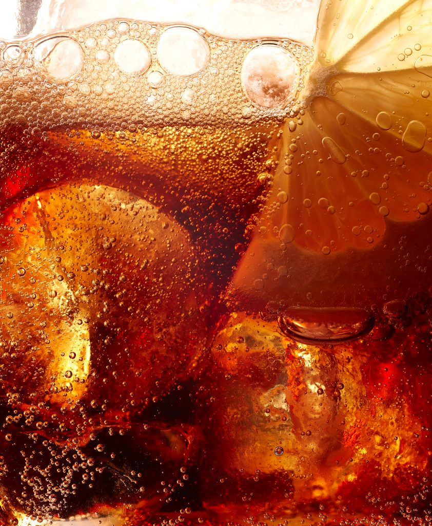 Close up image of coke with ice and a slice