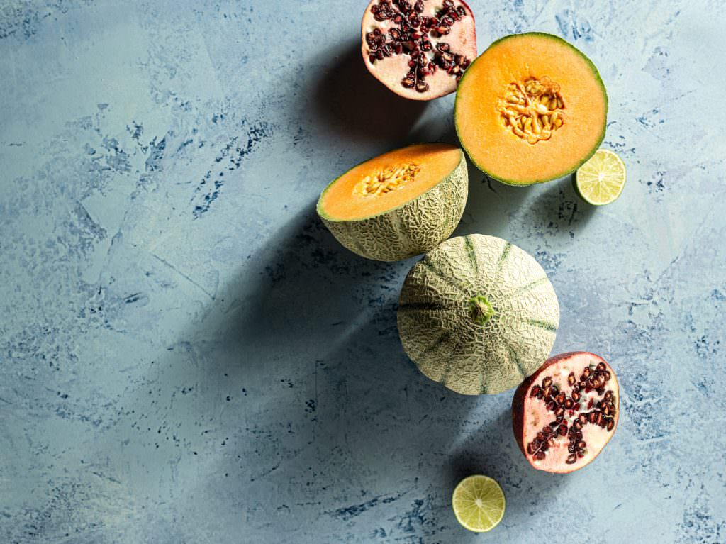 Gala melon and fruits photographed on a blackvelvet styling background