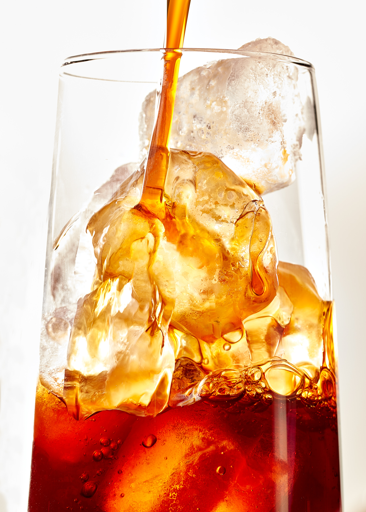 Iced coffee pouring into a glass
