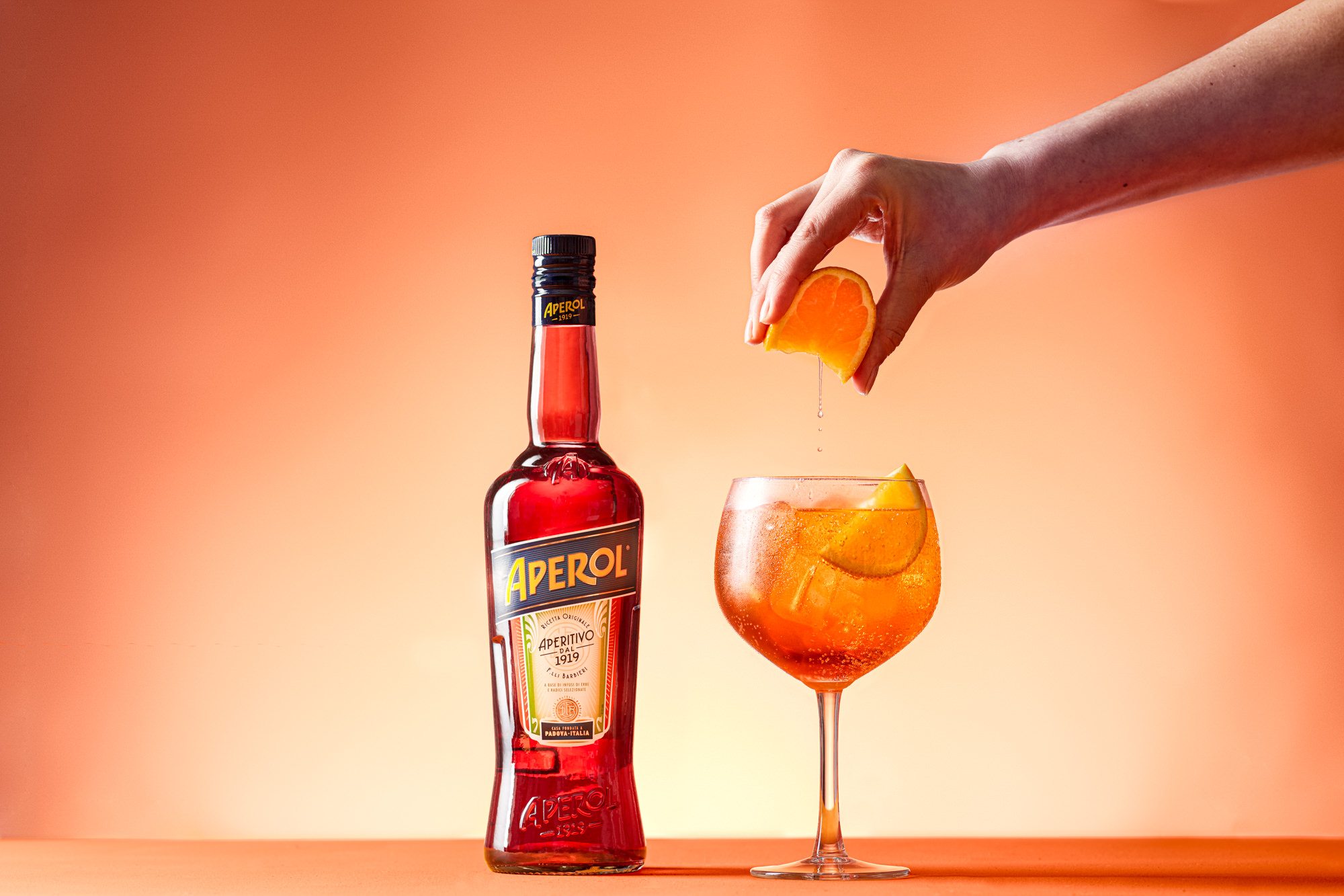 Aperol spritz with orange being squeezed into it