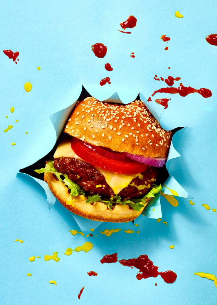 Beef Burger food photo exploding through blue paper