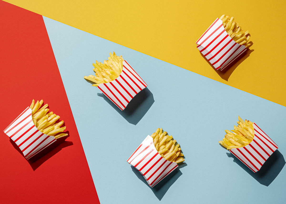 Pop art photography of french fries on yellow blue and red background