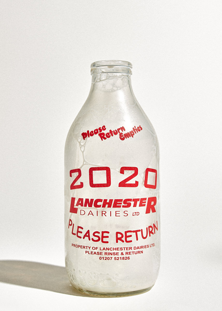 Milk bottle being rested with bubbles of milk after fast pour