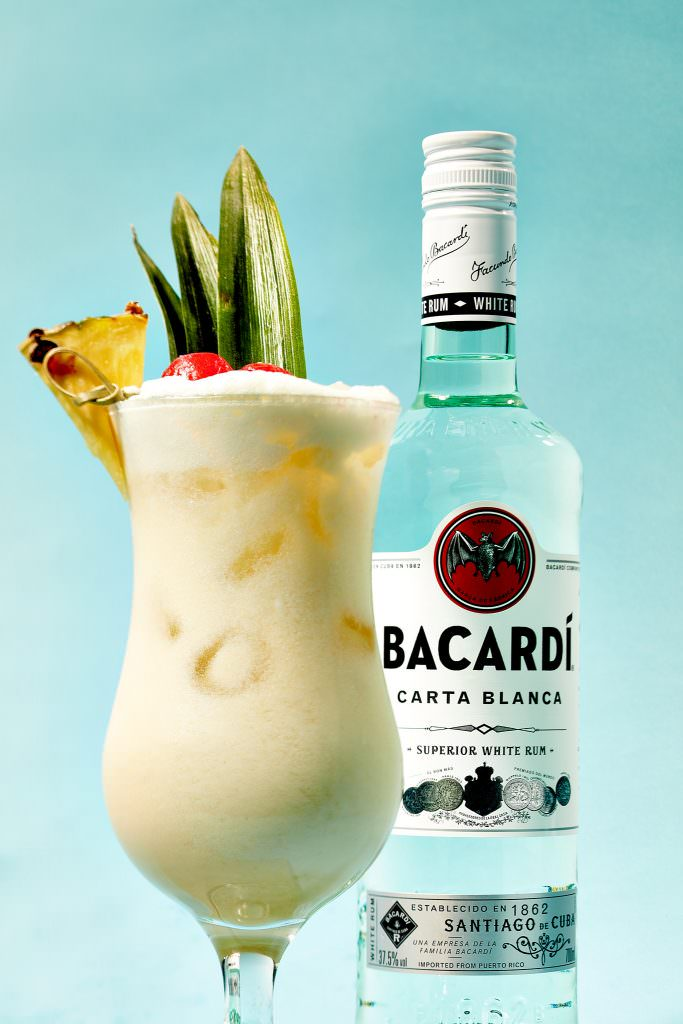 Drink photography of a pina colada and spirit bottle
